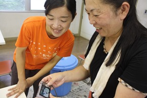 山田清美(左)因為藝術祭得以回到家鄉工作,她開心地看著當地居民分享參與藝術品創作的經驗