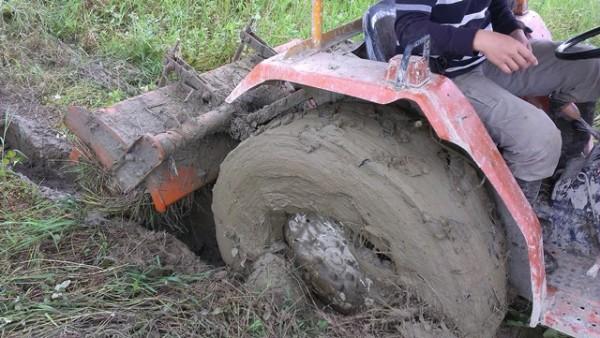 休耕十多年後,第一次整地就接連「着車」三次,曳引機的大輪陷入軟土內沾滿泥濘。