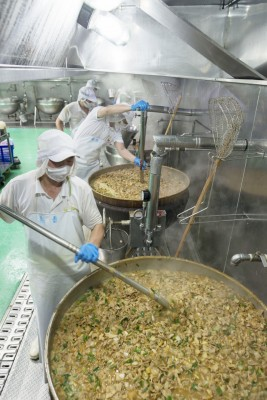 團膳公司的中央廚房裡,廚師費力烹煮大鍋菜。沒有自設廚房的學校將午餐製作與食安把關皆外包給了廠商。