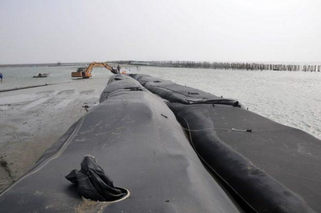 北門王爺港沙洲復育工程的「沙腸袋施工法」。(記者邱景威攝)