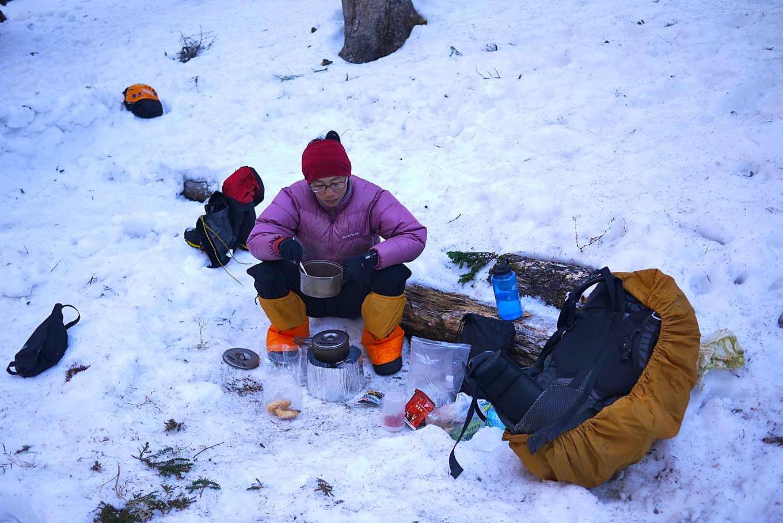 林乙華在雪地中獨自炊煮