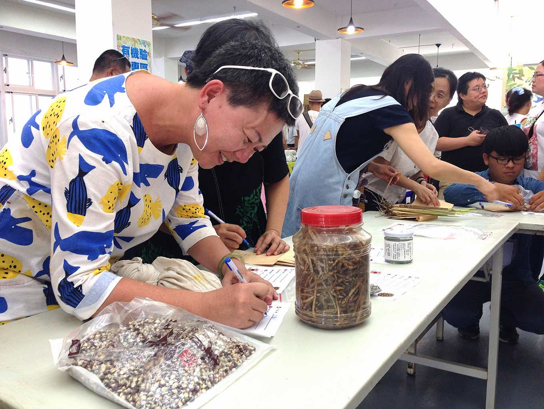 (左一)幫農友的種子寫下資訊(攝影/賴怡方)