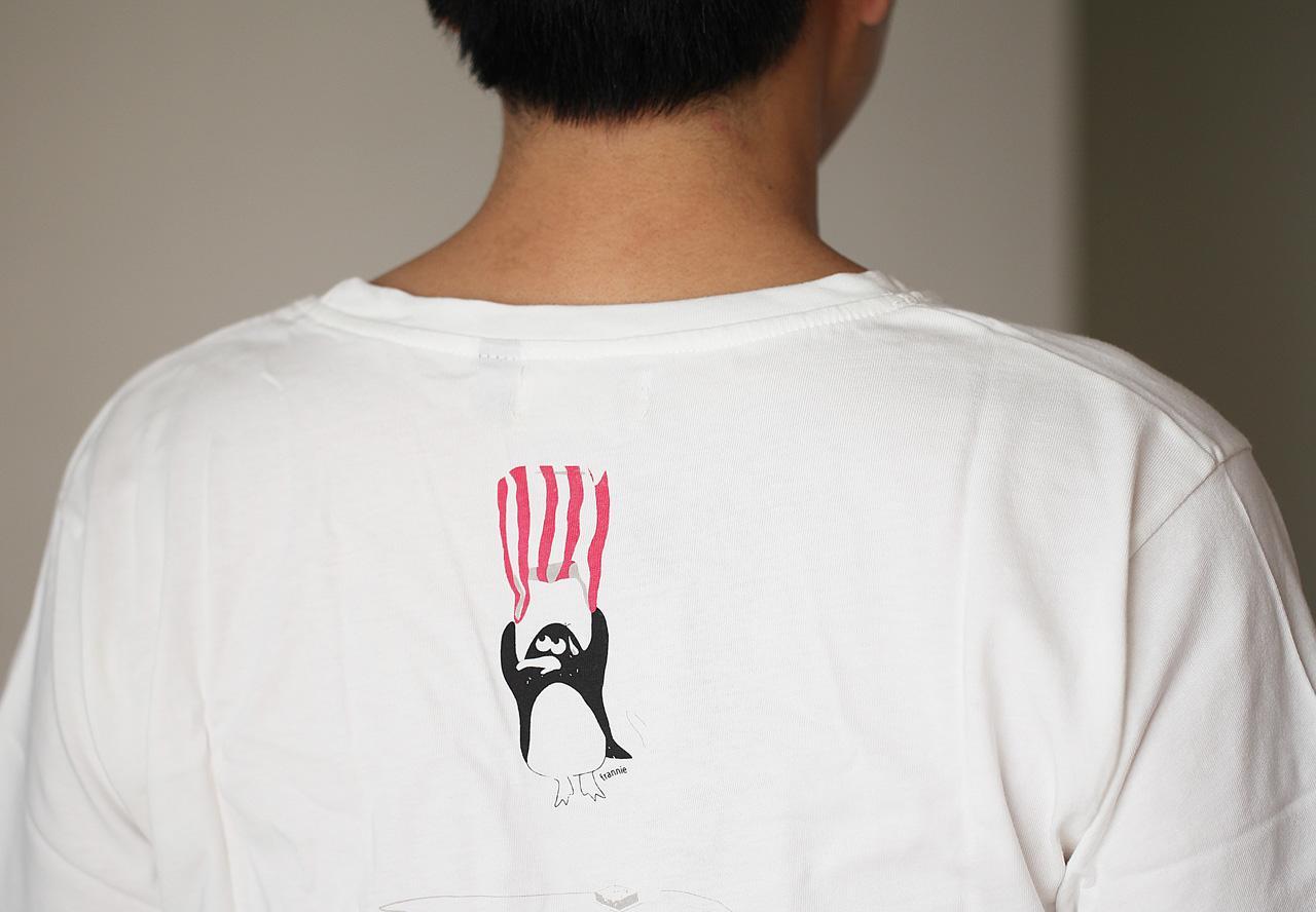 背後圖樣是一個帶著紅白塑膠袋降落的企鵝