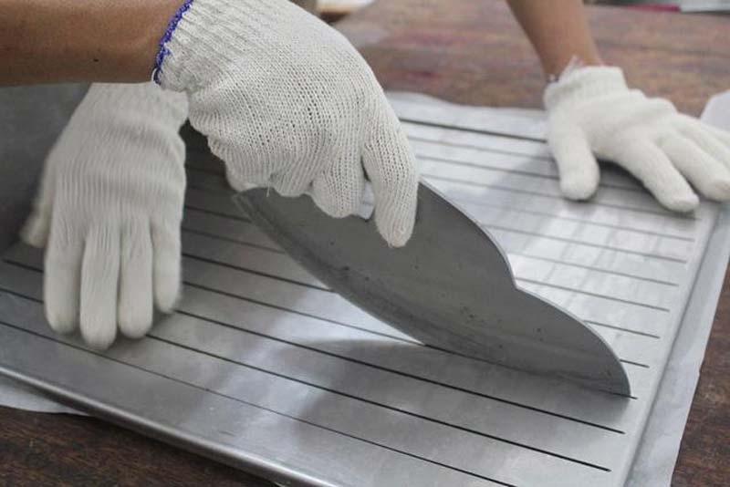 蓋上特製的切割對齊版,用特製的圓刀大力地切割花生糖。